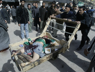 IRAQIS PUSH AN INJURED SHI'ITE PILGRIMS ON A CART AFTER EXPLOSIONS IN KERBALA.