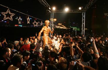 Fans of Hong Kong martial arts movie star Bruce Lee take photos around statue in Hong Kong