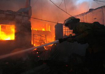 A firefighter tries to extinguish a fire, which hit a squatters area and destroyed more than a dozen dwellings, in Pasay City