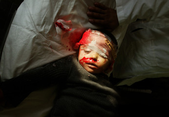 BODY OF BABY BOY KILLED DURING ATTACK ON GAZA LIES WRAPPED IN BLANKETS.