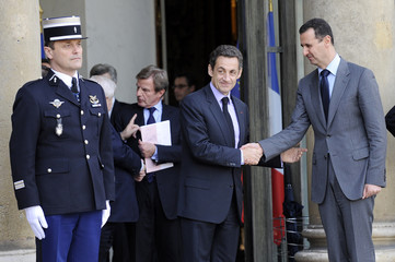 France's President Nicolas Sarkozy escorts Syria's President Bashar al-Assad following a meeting at Elysee Palace in Paris