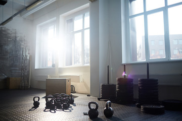 Background image of gym equipment: kettlebells wooden boxes and tire stands in bright sunlight