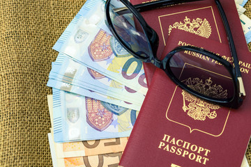 Passports with european union currency and sunglasses on a map background. Travel concept