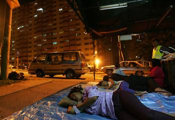 Malaysian family sleep on street outside after earth tremor in Kuala Lumpur.