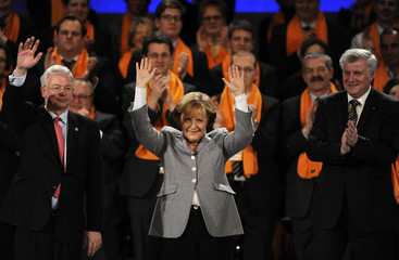 Hesse's state PM and top candidate for his conservative CDU, Koch, German Chancellor Merkel and Bavarian state PM Seehofer react to the applause in Frankfurt