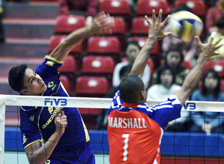 BRAZIL'S NASCIMENTO SPIKES AGAINST CUBAN MARSHALL DURING MEN'S WORLDGRAND CHAMPION CUP IN TOKYO.