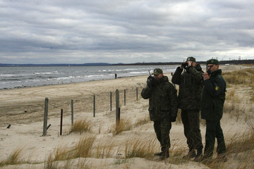 A German federal police man and Polish border guards scan the area near at beach at the German-Polish border near the German town of Ahlbeck
