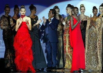 Italian designer Valentino (C) applauds with his models at the end of his Autumn-Winter 2002-2003 hi..