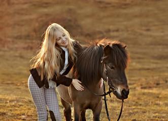 Portrait of little girl with her pony. Blonde, farm, jockey. Sunny backlight