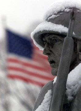 Snow covers a statue at the Korean War memorial with an American flag in the background in Washingto..