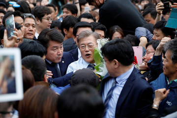 Moon Jae-in, the presidential candidate of the Democratic Party of Korea, is surrounded by his supporters as he leaves after his election campaign rally in Goyang