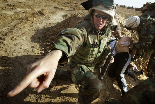 WOUNDED IRAQI MAN IS TREATED BY U.S. MARINES IN CENTRAL IRAQ.