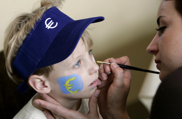 A child has his face painted with the euro symbol to mark next year's adoption of the common currency by Malta and Cyprus during a ceremony at the European Commission headquarters in Brussels