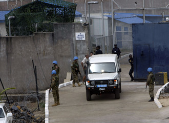 Former Liberian president Charles Taylor is led in a van from a prison to a special court in Freetown