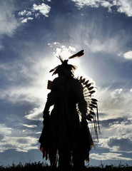 An Oglala Lakota warrior is silhouetted against the late afternoon sky during a three-day PowWow on ..