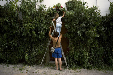 Man and his daughter decorate their house with flowers in El Gastor