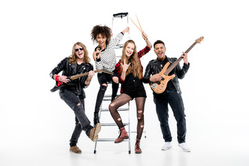 Young rock and roll band posing with ladder holding microphone and guitars isolated on white