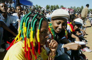 Young Ethiopian girls who have braided their hair with rasta colours, sit among thousands of ...