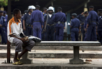 A Congolese boy looks at Congolese policemen from a bus stop in Kinshasa