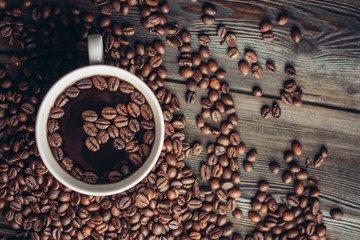 coffee beans on a wooden background, cup