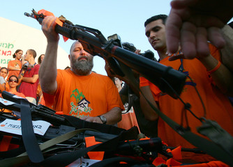 Jewish settlers hand over their weapons to the Israeli army at the Jewish settlement of Netzer Hazani.