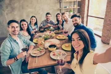 Hispanic cute girl is making selfie with her friends at the birthday  party on her phone`s camera. Everyone are smiling and holding the glasses of red wine