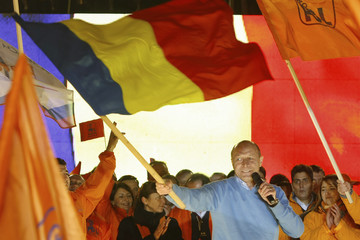 Romania's incumbent President Traian Basescu waves the national flag at the end of an electoral meeting in Bucharest