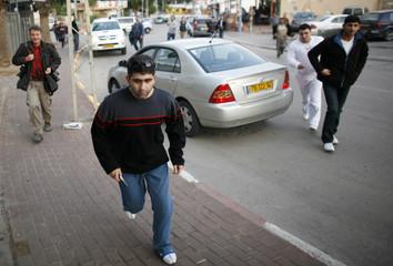 Israelis run towards a bomb shelter in Sderot