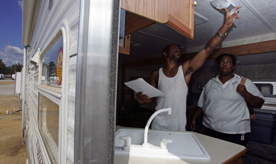 Former resident of Metarie tests a light as wife looks on shortly after arriving at their trailer home in Baker
