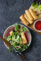 Fried spring rolls with red pepper sauces, served in traditional china plate with fresh green salad and wooden chopsticks over black texture background. Flat lay, space. Asian food