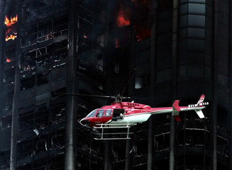 An helicopter flies over the burnt upper half of the 56-floor East Tower of the Parque Central ...