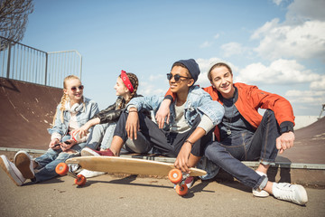 Happy teenagers group sitting together and talking at skateboard park