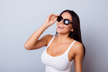 Young cute latin american lady with beaming smile in stylish spectacles is standing on the light blue background. She is full of dreams and fantasies