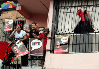 Supporters of Venezuelan President Chavez greet him during a campaign rally in Caracas