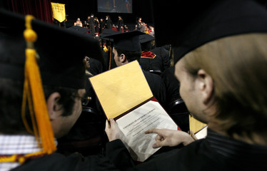 A graduating student looks at his diploma at the 2007 USC School of Cinematic Arts commencement at the University of Southern California in Los Angeles