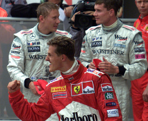 German Formula One driver Michael Schumacher of the Ferrari racing team (C) celebrates after winning..