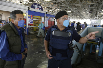 Policeman wearing surgical mask directs passengers at Chabacano subway station in Mexico City