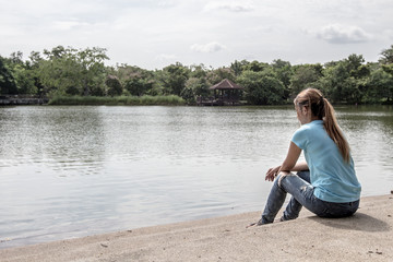 Young Asian woman sit near the Lake.