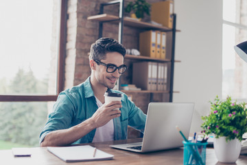 Smiling handsome worker in glasses drinking coffee while watching video on his laptop at office