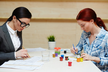 Waist-up portrait of two pretty women concentrated on work: ambitious architect drawing project with pencil and ruler while creative designer sitting opposite her and creating colorful picture