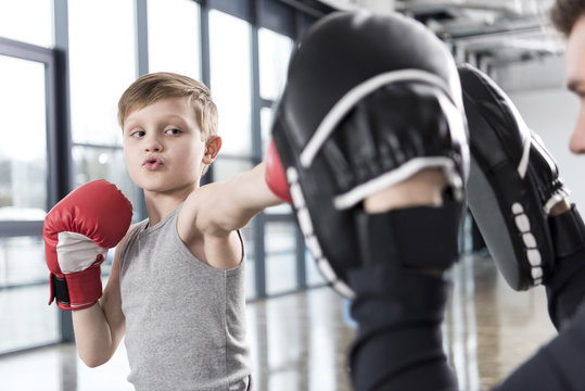 young boy boxer practicing punches with coach