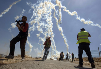 Tear gas canisters fired by Israeli soldiers land near journalists and protesters during a protest in Bilin near Ramallah