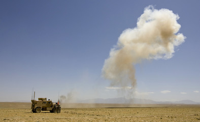 U.S. Army soldiers stand behind a vehicle as cloud of dust rise into air after controlled detonation outside FOB Shank in Logar Province