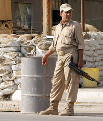 Private security guard stands at a sandbag emplacement at the entrance of Japan's embassy in Baghdad.