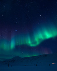 The polar Northern aurora borealis lights in Norway Svalbard in the mountains
