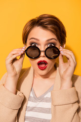 Omg! Close up portrait of amazed girl with red pomade in stylish sunglasses and casual wear on the bright yellow background