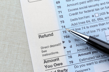 Tax refund document and pen on light background