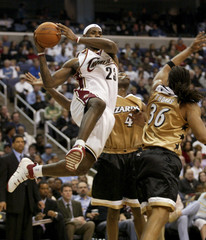 LeBron James of the Cavaliers drives past Antawn Jamison and Etan Thomas of the Wizards in Washington