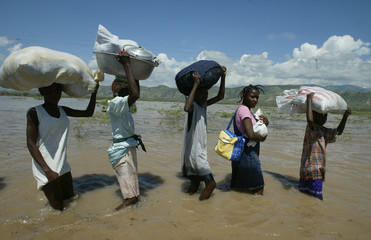 Haitians wade across submerged highway in Gonaives.