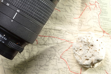 Telephoto lens and white color coral put on old and vintage paper map.